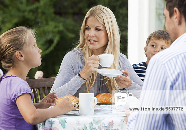 Familie am Kaffeetisch auf Terrasse