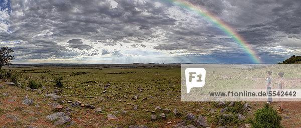 Zwei Mädchen  etwa 13 und 18 Jahre schauen über das Masai Mara Naturschutzgebiet mit Regenbogen  Kenia  Ostafrika  Afrika  ÖffentlicherGrund
