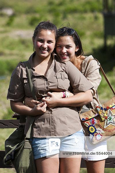 Zwei Mädchen  etwa 13 und 18 Jahre  stehen mit Safarioutfit an einem Geländer  Masai Mara Naturschutzgebiet  Kenia  Ostafrika  Afrika  ÖffentlicherGrund