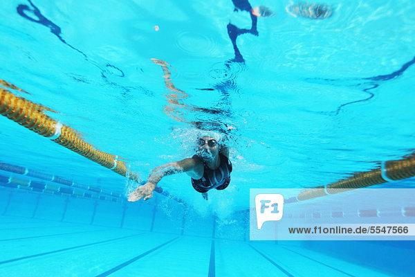 Unterwasseraufnahme Frau schwimmt in Schwimmbad