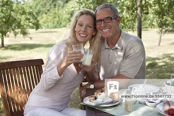 Fröhliches reifes Paar sitzt im Freien am Frühstückstisch