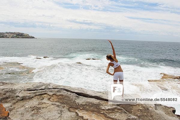 Young Woman Exercising at Seashore