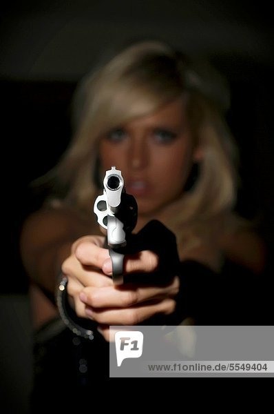 Woman in fear pointing a gun at viewer