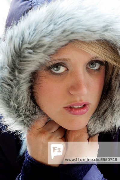 Close in shot of a 31 year old blond woman with a serious expression  eyes to camera wearing a hooded coat
