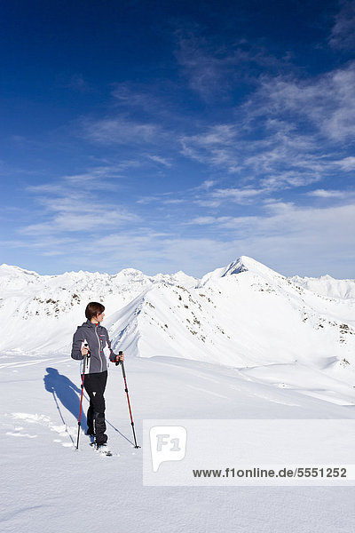 Bergsteigerin im Schnee auf dem Terner Jöchl oberhalb von Terenten  Pustertal  hinten das Mutenock  Südtirol  Italien  Europa