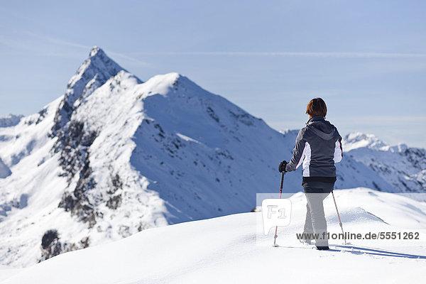 Wanderin im Schnee auf der Röthenspitz oberhalb vom Penser Joch  hinten der Gipfel vom Penser Weißhorn  Sarntal  Südtirol  Italien  Europa