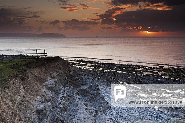 Sonnenuntergang an einem bewölkten und regnerischen Abend am Kilve Beach Strand  Blick von den Klippen auf den Bristolkanal  Großbritannien  Europa