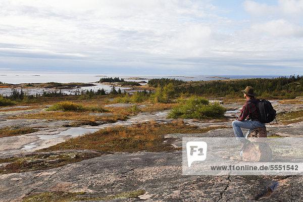 Tourist enjoying view near Natashquan  Duplessis district  Quebec  Canada