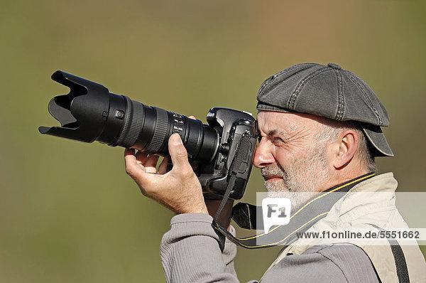 Mann mit Kamera  Fotograf beim Fotografieren