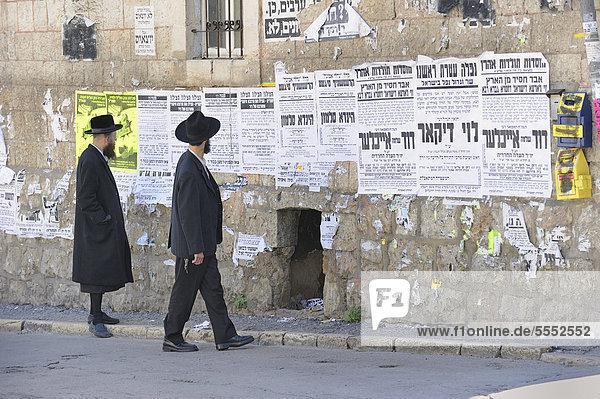 Orthodoxe Juden lesen Wandzeitungen im Stadtviertel Me'a Sche'arim oder Mea Shearim  Jerusalem  Israel  Vorderasien