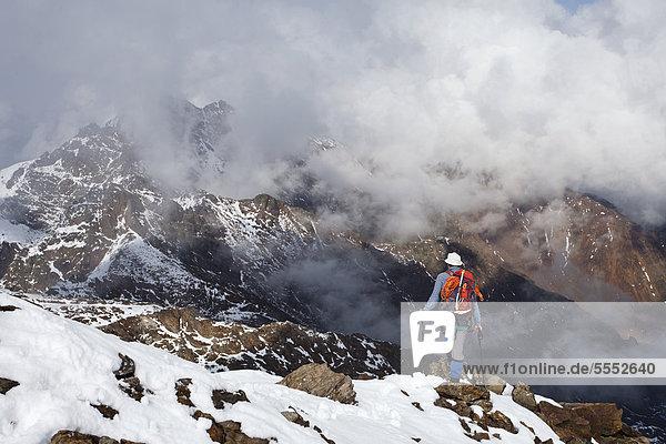Wanderer auf der Lorcherspitz oberhalb des Grünsees  hinten die Weißbrunnspitze und Zufrittspitze im Hochnebel  Südtirol  Italien  Europa Wanderer auf der Lorcherspitz oberhalb des Grünsees, hinten die Weißbrunnspitze und Zufrittspitze im Hochnebel, Südtirol, Italien, Europa