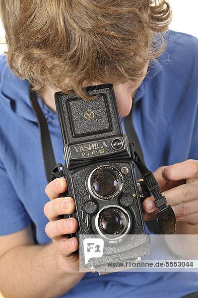 Junger Mann fotografiert mit einer analogen zweiäugigen 6x6 TLR Kamera