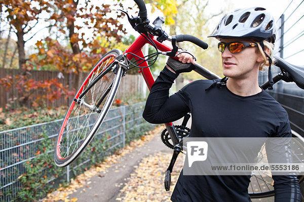 Cyclist carrying bike