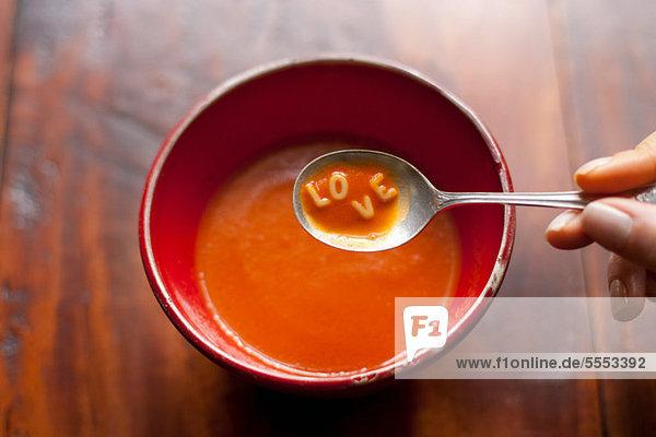 Frau hält Löffel voll Suppe mit Buchstaben LOVE
