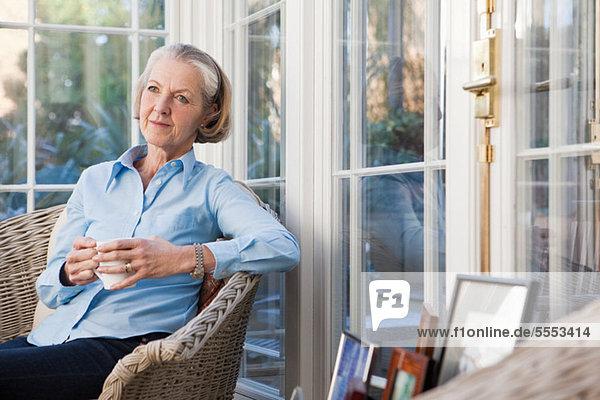 Senior Woman relaxing mit Heißgetränk