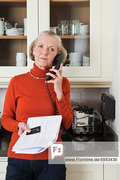 Seniorin am Telefon mit Auszug und Kreditkarte