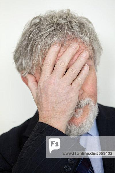 Älterer Mann mit handbedecktem Gesicht