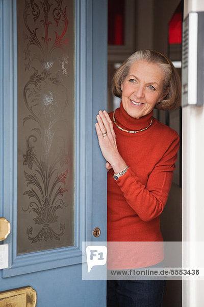 Seniorin beim Öffnen der Haustür