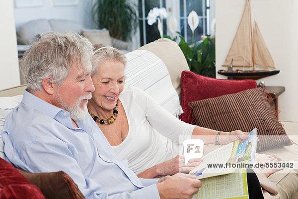 Seniorenpaar schaut sich die Reisebroschüre an