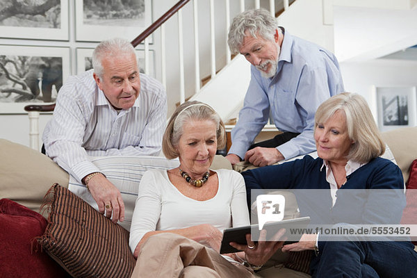Seniorenfreunde mit digitalem Tablett