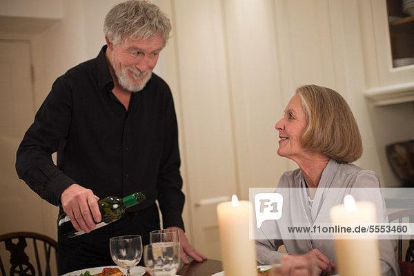 Mann gießt Wein für die Frau