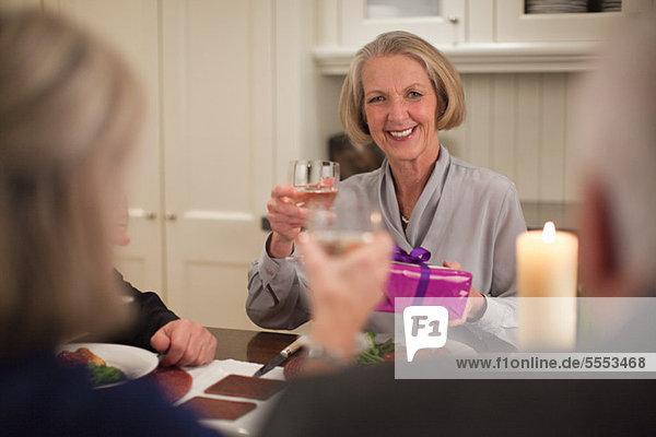 Senior Woman at Dinner-Party mit Geschenk