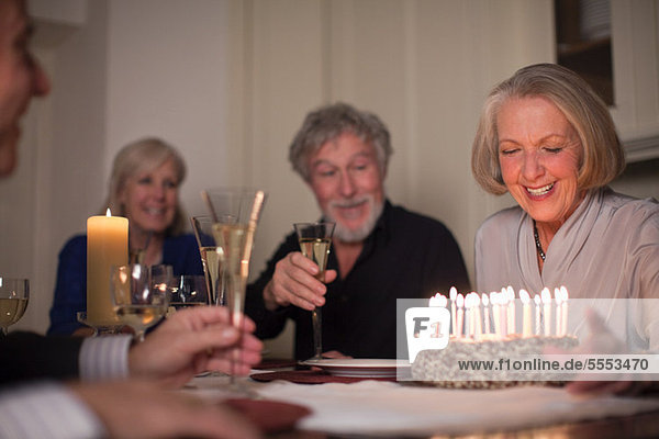 Seniorin und Freunde mit Geburtstagskuchen