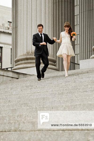 Neuvermähltes Paar absteigende Stufen zusammen