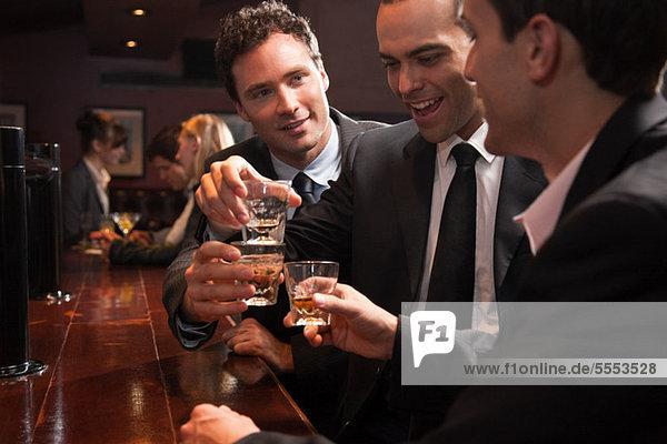 Three businessmen drinking at a bar