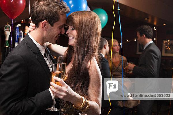 Zärtliches junges Paar auf der Party mit Champagner