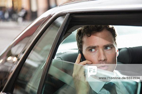 Businessman in Car auf Handy