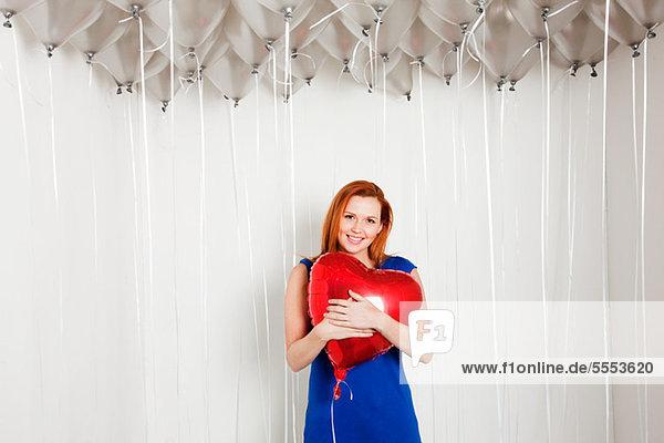 Junge Frau mit herzförmigem Ballon