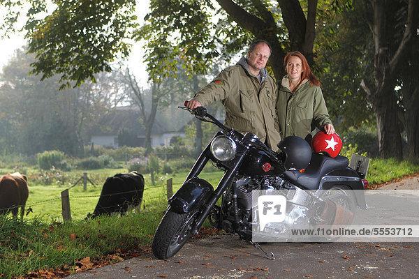 Paar an einem Motorrad auf einer Landstraße