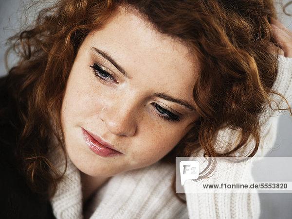 Nachdenkliche Teenagerin mit lockigen Haaren