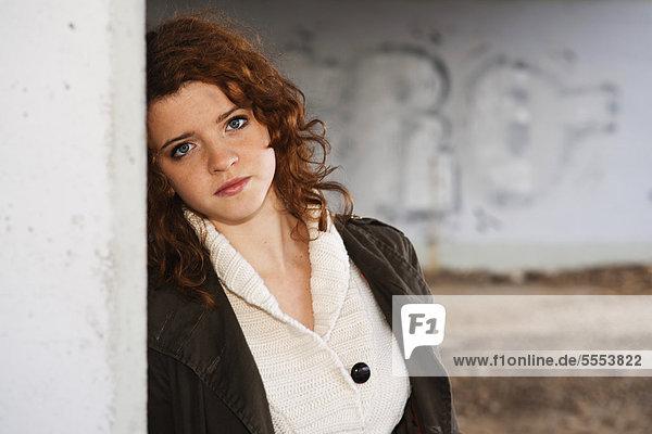 Teenagerin mit lockigen Haaren lehnt an einer Wand  Portrait