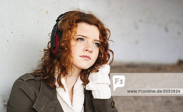 Teenagerin mit lockigen Haaren hört Musik