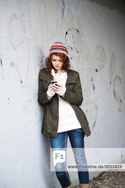 Teenagerin im Freien schaut auf ihr Handy