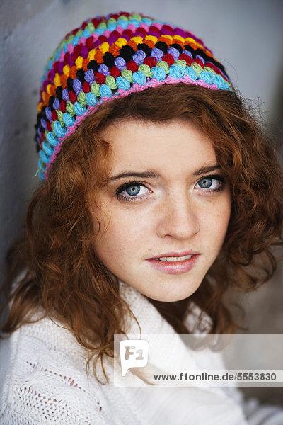 Teenagerin mit lockigen Haaren trägt eine Wollmütze  Portrait