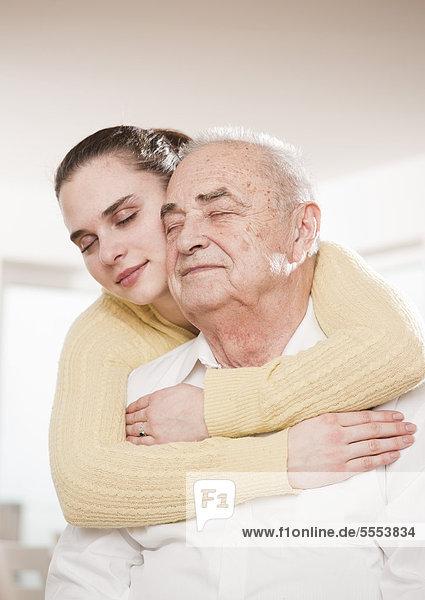 Junge Frau umarmt Senior