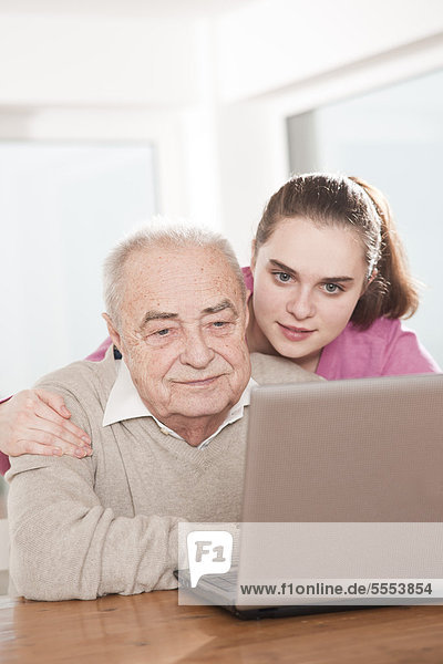 Junge Frau und Senior am Laptop