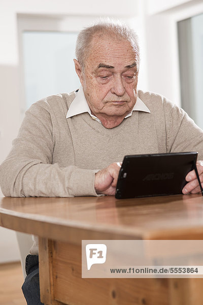Senior benutzt ein Netbook am Tisch