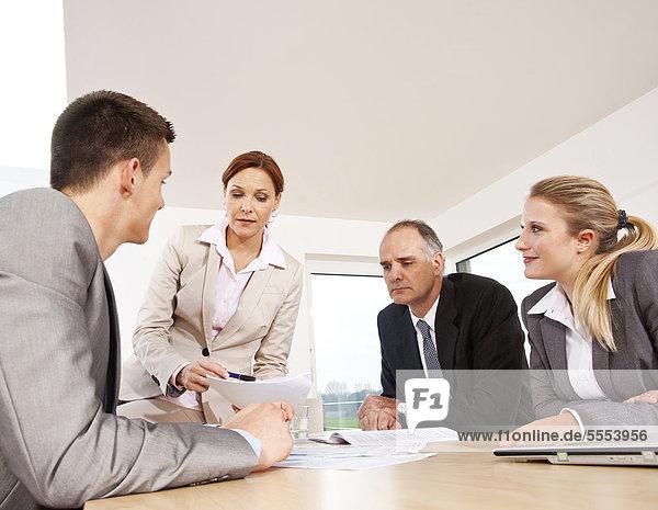 Vier Geschäftsleute im Konferenzraum unterhalten sich