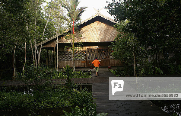 Indonesia  Borneo  View of hotel Rimba Logde with man walking in front of it