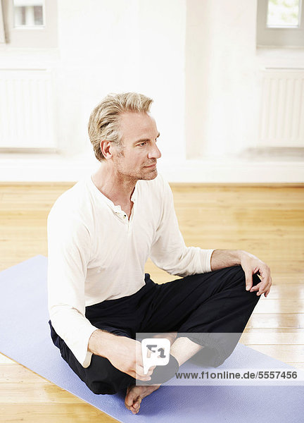 Mature man sitting on mat and looking away