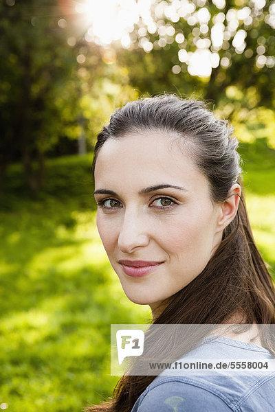 Lächelnde Frau im Park stehend