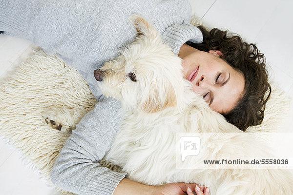 Frau entspannt sich mit Hund auf dem Teppich