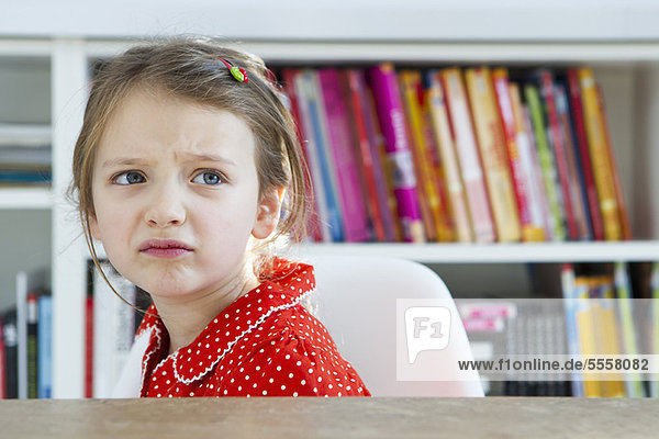 Frowning girl sitting at table