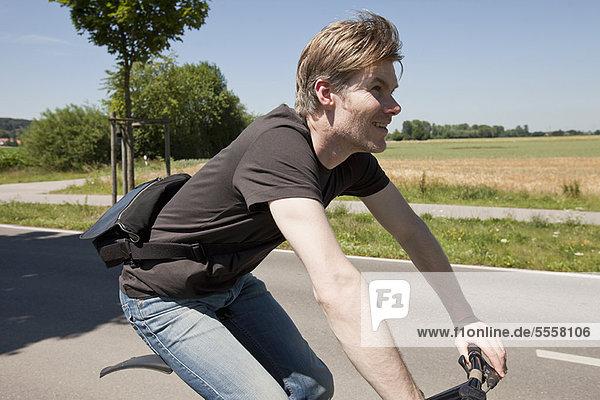 Mann mit dem Fahrrad auf der Landstraße