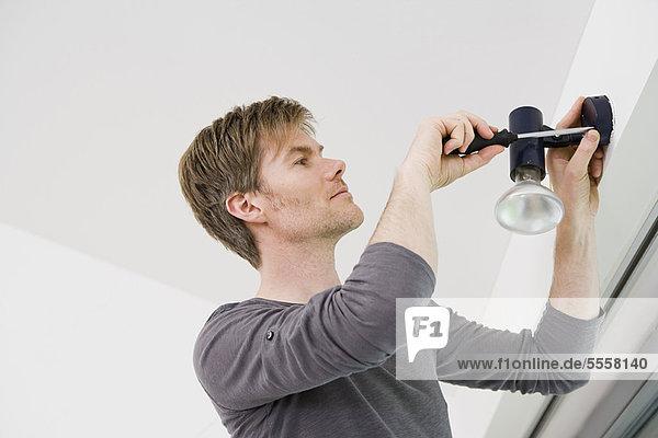 Mann beim Einbau der Leuchte im Haus