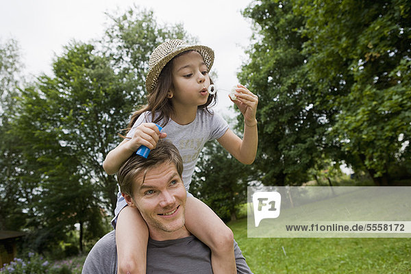 Girl with bubbles on fathers shoulders